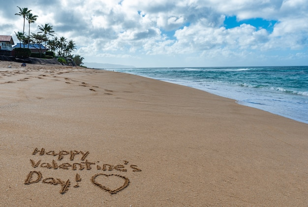Happy valentine's day with a heart drawn in the sand on the beach