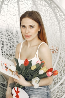 Happy valentine's day. young lady sit in a chair with tulips and greeting card.