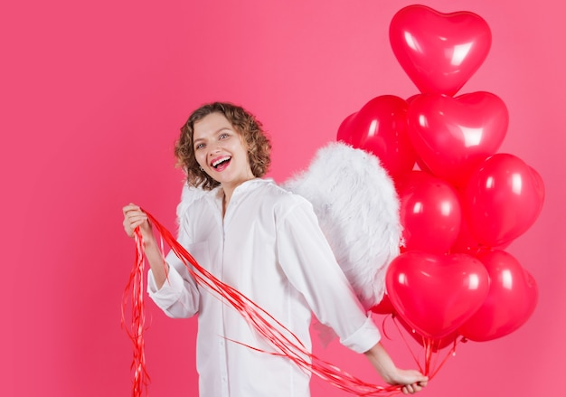 Happy valentines day. angel woman with red heart shape balloons. smiling female cupid with wings.
