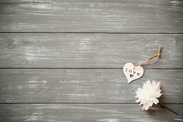 Happy valentines day background. decorative white wooden heart on grey rustic, whith flowers, valentine's concept.