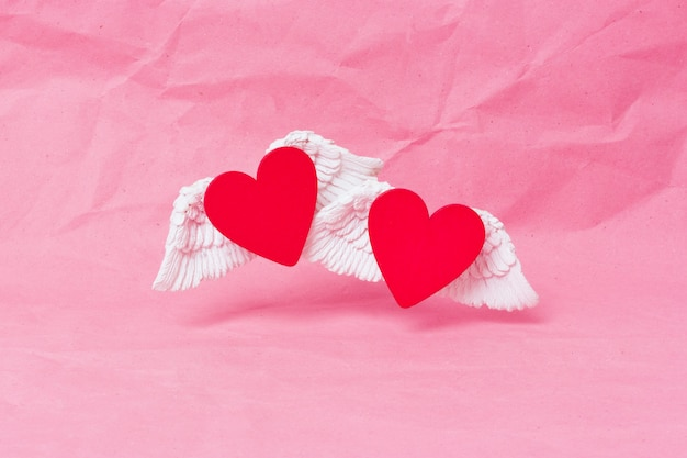 Happy valentines day banner. a red wooden heart with white voluminous wings soars over a pink crumpled paper background. minimalism. place for text