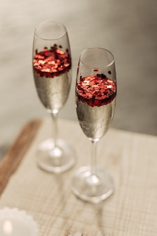 Happy valentines day celebration concept. close up of 2 two glasses with sparkling champagne and red heart shaped confetti. love potion in glass. the concept of wedding, lovers day. romantic date