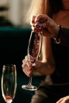 Happy valentines day celebration concept. man pouring heart shaped confetti in woman's empty champagne glass. love potion in glass.