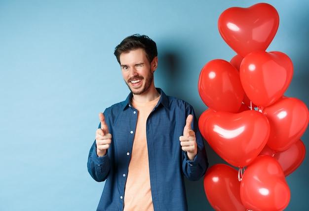 행복한 발렌타인 데이. 건방진 남자 친구 윙크와 파란색 배경에 빨간색 로맨틱 풍선과 함께 서 카메라에 손가락을 가리키는. 공간 복사