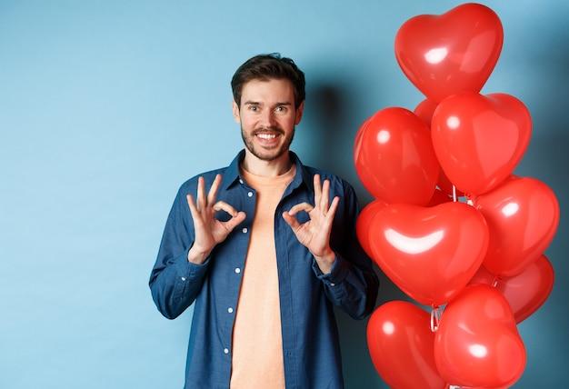 행복한 발렌타인 데이. 괜찮은 제스처를 보여주는 쾌활한 남자 친구와 연인, 파란색 배경에 빨간색 하트 풍선과 함께 서있는 좋은 것을 칭찬합니다.