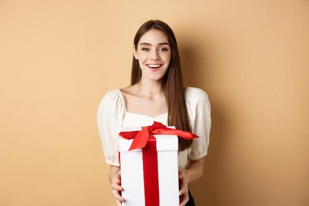 행복한 발렌타인 데이. 연인에게 깜짝 선물을주고, 카메라를보고, 상자에 선물을 들고, 베이지 색 배경에 서있는 밝은 웃는 소녀.