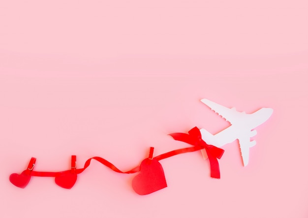 Happy valentines day. children's plane on a pink background with red heart
