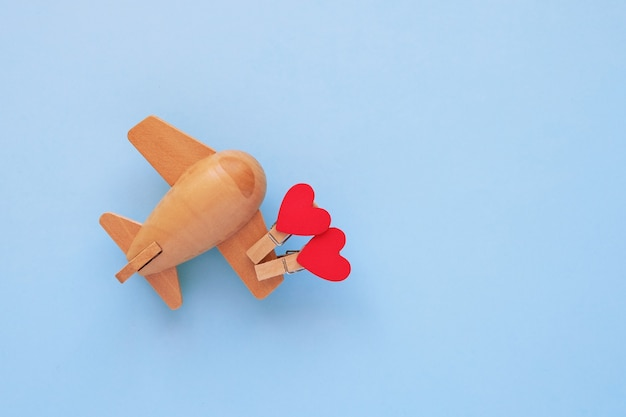 Happy valentines day concept. eco wooden children's plane on a blue background with red heart.
