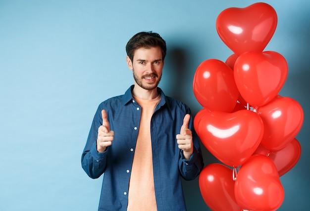 행복한 발렌타인 데이. 카메라에서 손가락을 가리키고 웃 고, 파란색 배경에 풍선과 함께 서 자신감 남자.