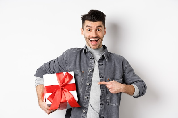 С днем святого валентина. возбужденный кавказский парень, указывая на подарочную коробку от любовника, улыбается и выглядит изумленным, покупает подарки на романтическое свидание, белый.