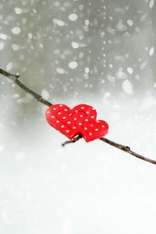 冬の雪に覆われた木の枝に幸せなバレンタインデーのグリーティングカードやバナーの赤いハート...