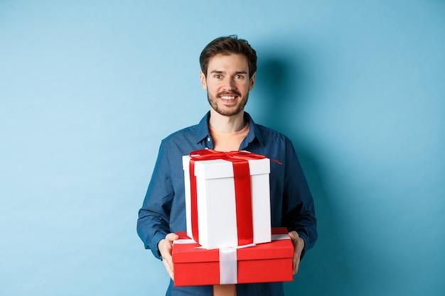 С днем святого валентина. красивый парень держит подарки для любовника на годовщину романтического свидания, стоя на синем фоне.