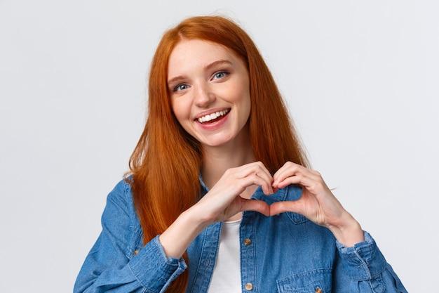 행복한 발렌타인 데이, 사랑. 귀 엽 고 부드러운 로맨틱 빨간 머리 여자 친구 보여주는 마음 기호, 동정심 고백, 열정 표현 또는 놀라운, 놀라운 작품에 감탄, 감사, 흰 벽에 서