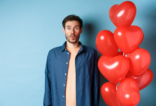 Happy valentines day. man looking surprised and interested at camera, saying wow, standing near red hearts balloons, blue background.