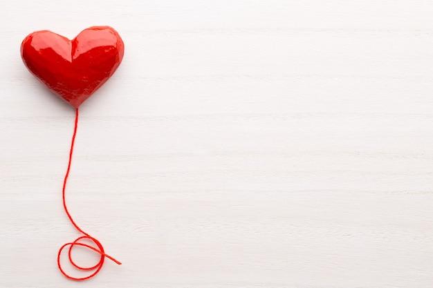 С днем святого валентина. сердце красной ленты на деревянной предпосылке.
