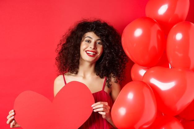 С днем святого валентина. романтичная девушка в платье ждет настоящей любви, показывая большое красное сердце и стоя возле воздушных шаров на красном фоне.