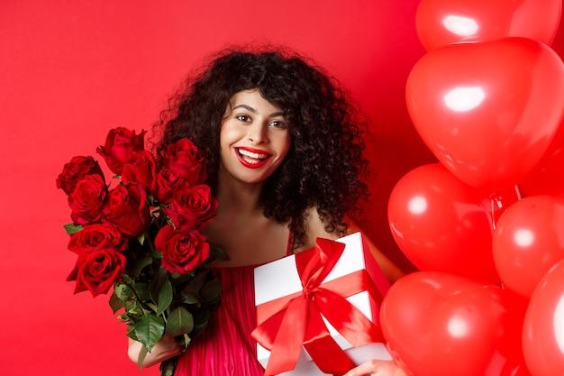 행복한 발렌타인 데이. 연인에서 선물 로맨틱 소녀, 장미와 선물 상자의 꽃다발을 들고 스튜디오 배경에 귀여운 빨간 하트 근처에 서.
