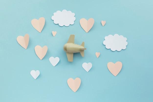幸せなバレンタインデー。紙の白い雲と紙のピンクのハートと青い背景のおもちゃの飛行機の航空機。