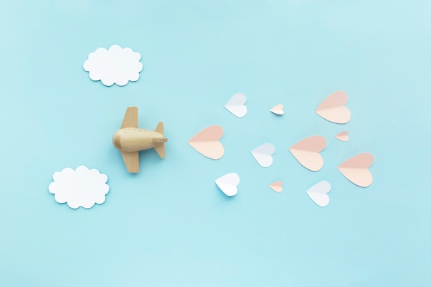 幸せなバレンタインデー。白い雲とピンクのハートと青い背景のおもちゃの飛行機の航空機。