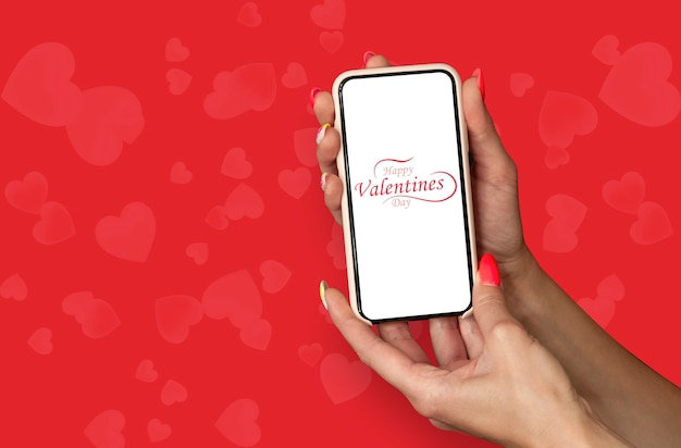Happy valentines day. a woman holds a mockup of a smartphone in her hands on the background of a hearts.