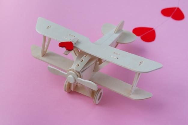 행복한 발렌타인 데이. 붉은 마음으로 분홍색 표면에 나무 어린이 비행기와 심장 모양의 화환