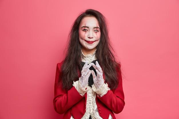 幸せな吸血鬼の女性は悪魔の計画と何かをする意図を持っていますハロウィーンの化粧を着て、バラ色の壁に対して屋内で仮面舞踏会の衣装のポーズをとる