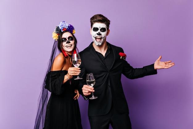 紫色の背景にワインを飲む幸せな吸血鬼。伝統的なメキシコのゾンビの服装のカップルのスタジオ写真。