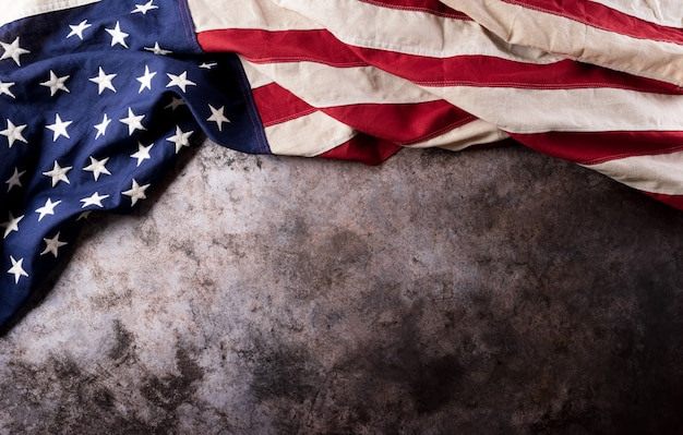 Happy veterans day concept american flags against a dark stone  background
