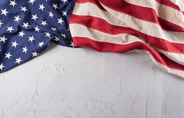 Happy veterans day concept. american flags against a white stone  background. november 11.