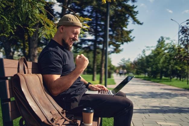Счастливый победоносный бородатый мужчина сидит на скамейке на открытом воздухе, глядя на ноутбук, жестикулируя да побеждает победителя