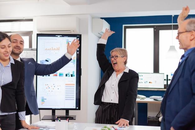 会議室で立ち上がった手で祝うスタートアップ企業の幸せな勝利のビジネスマン