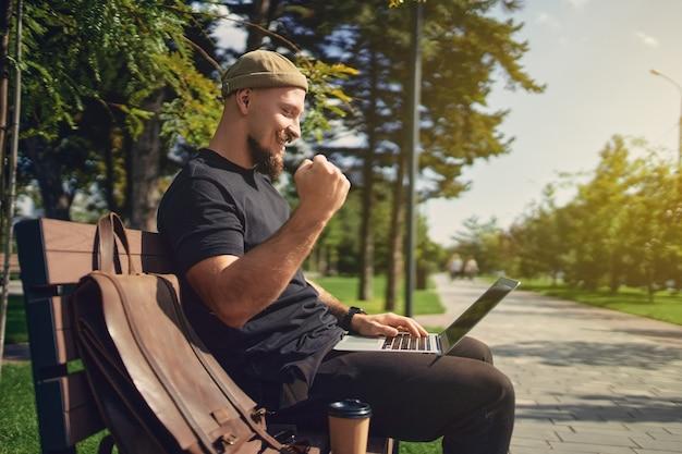 Счастливые миллениалы-победители сидят на скамейке на открытом воздухе и смотрят на ноутбук, жестикулируя: да, победитель