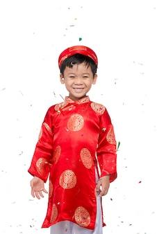 Счастливый вьетнамский мальчик в красном ао дай празднует новый год с конфетти. азиатский ребенок празднует новый год