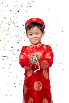 Happy vietnamese boy in red ao dai celebrating new year with confetti. asian kid celebrating new year