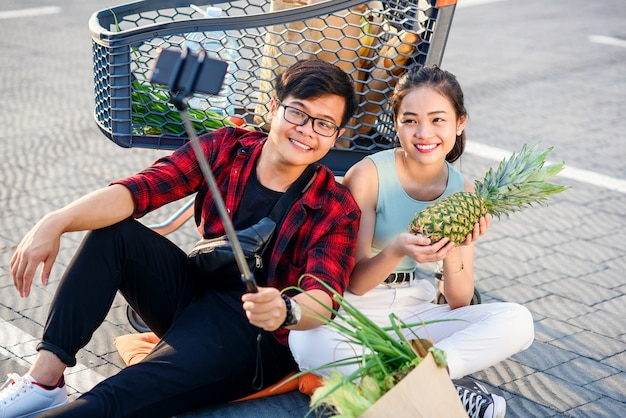 Happy vietnamese couple sitting on the ground near big shopping centre and making selfie photo with peanapple.