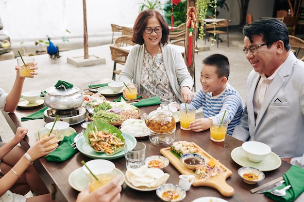 Happy vietnamese family sitting at big dinner table in backyard, eating traditional dishes and talking when celebrating lunar new year