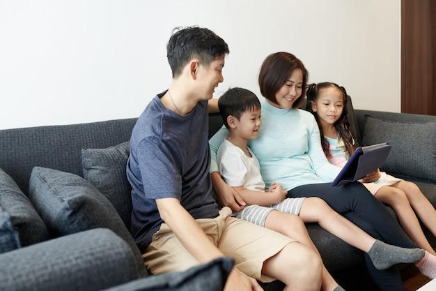 一緒に時間を過ごし、デジタルタブレットでアニメーションビデオやブログを見て楽しんでいる2人の子供を持つ幸せなベトナムの家族 Premium写真