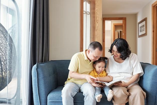 幸せなベトナムの父と母はソファに座って、一緒に面白い本を読んでいます