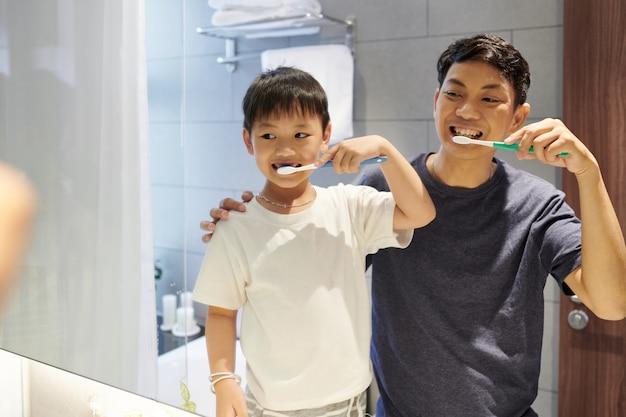 Счастливый вьетнамский отец и сын чистят зубы перед зеркалом в ванной по утрам
