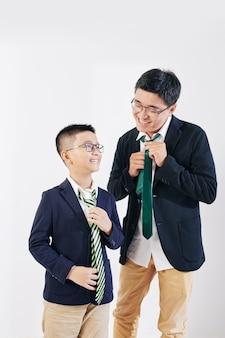 행복한 베트남인 아버지와 아들이 아침에 학교를 준비하고 일할 때 넥타이를 매고 있습니다.