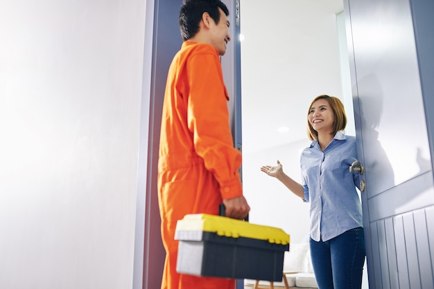 Happy vietnamese woman opening entrance door and inviting handyman inside