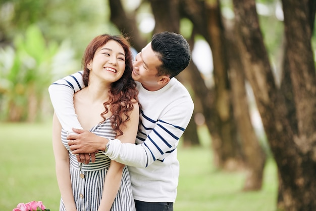 Happy vietnamese young man hugging his girlfriend from behind and kissing her on cheek