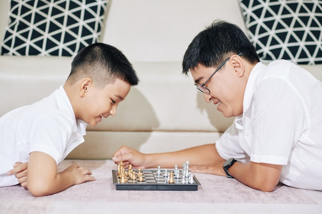 Happy vietnamsese father and son lying on sofa and playing game of chess