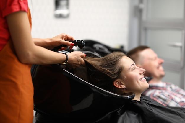 Счастливая посетительница салона красоты лежит, положив голову в черный умывальник, и ждет, пока парикмахер помоет волосы водой из душа.