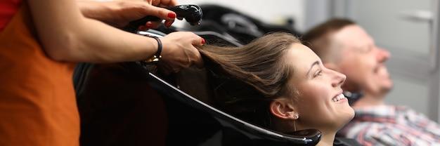 뷰티 살롱에 대한 행복한 방문자는 검은 색 세면대에 그녀의 머리와 거짓말