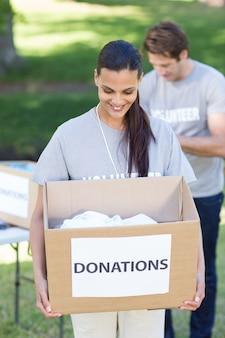 Счастливый добровольца брюнетка проведения пожертвования поле