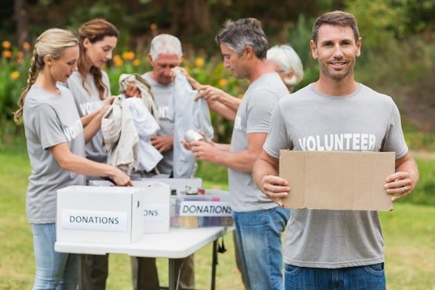 Счастливые семьи добровольцев, держащих пожертвования коробки