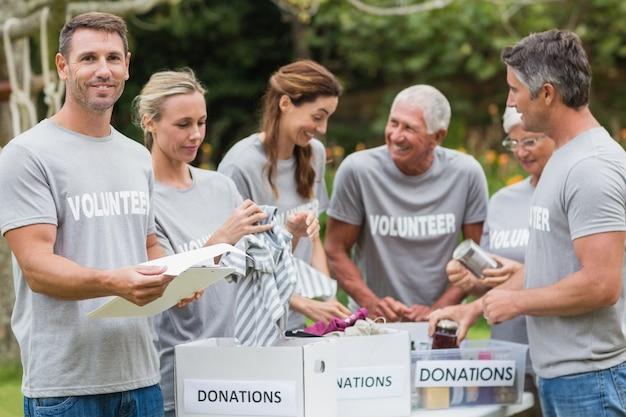 Счастливый добровольцем, глядя на коробку пожертвований