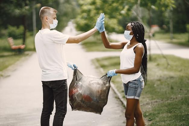 Volontari felici che si danno il cinque l'un l'altro dopo aver completato i compiti. ragazza afroamericana e ragazzo europeo.