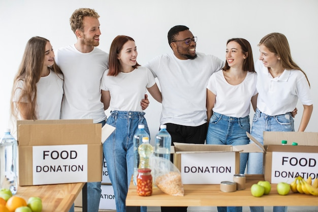 Счастливые волонтеры обнимают друг друга, готовя коробки для пожертвований